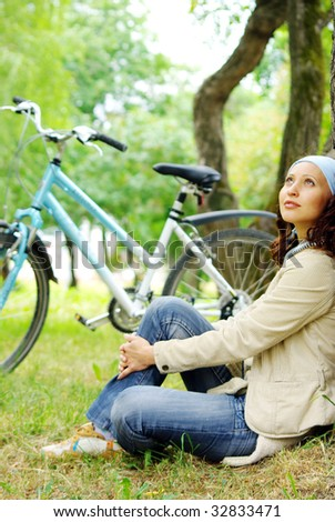 girl relaxing under green tree with her bicycle