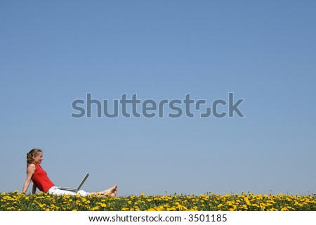 Girl relaxing with laptop outdoors, in a flowering dandelion field. - stock photo