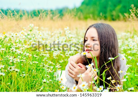 girl resting in a field of chamomile in a white dress