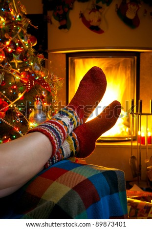 girl resting in a room with a burning fireplace and Christmas tree - stock photo