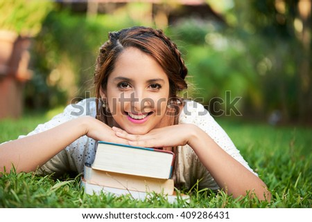 girl resting on top of books and smiling at the park