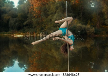 Girl revolves on the pole for dancing performing tricks. Around the forest and lake. - stock photo