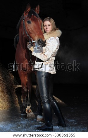 Girl rider near her brown horse in stable. get ready for winter riding