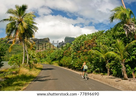 Girl riding a bicycle through the tropical  island Bora Bora , French Polynesia
