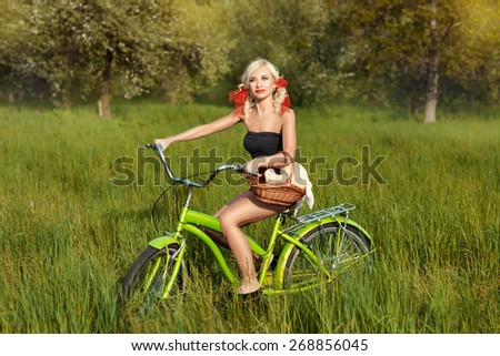 Girl riding a bike on the grass in the meadow. - stock photo