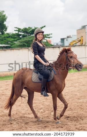 Girl riding a horse - stock photo
