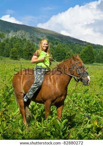 girl riding a horse bareback at mountains - stock photo