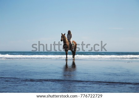 Girl riding a horse, riding a horse, coast of the ocean.