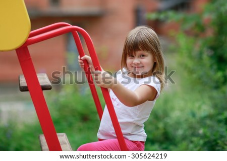 girl riding down the slide on the Playground, close-up - stock photo