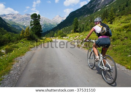 Girl riding fast on a bicycle in mountain area. Back view and motion blur - stock photo