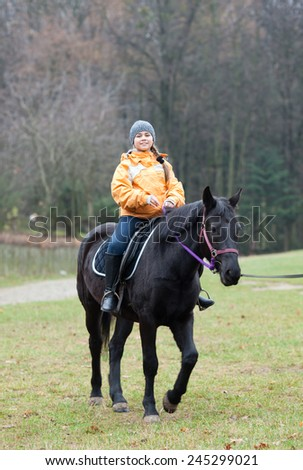 Girl riding her horse on the meadow - stock photo