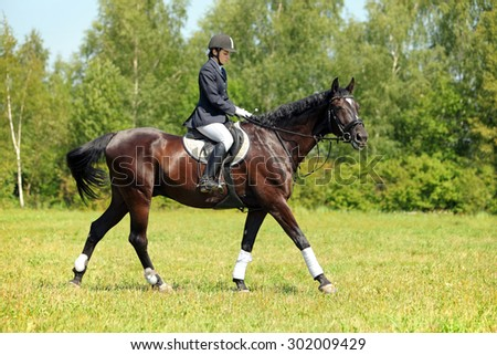 Girl riding horse in English riding attire and saddle on a sunny day - stock photo