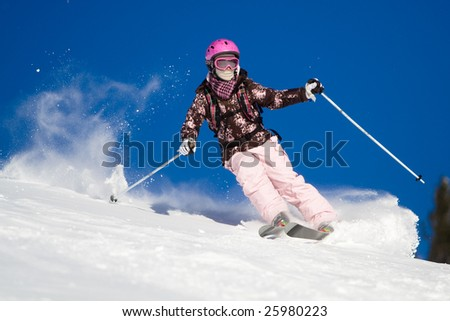 Girl riding on skis with bright blue sky on the background - stock photo
