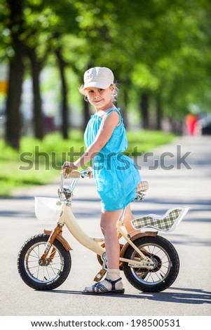 Girl riding on small two-wheeled bicycle - stock photo