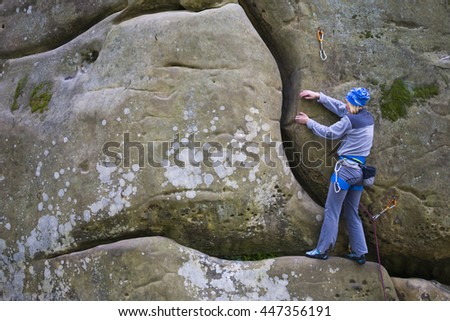 Girl rock climber climbs difficult route on the cliffs.