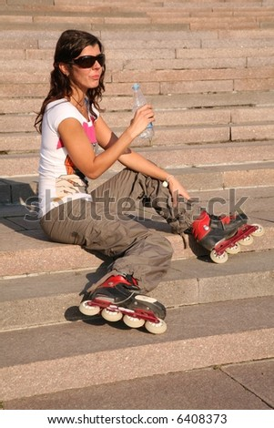 girl-roller sits on the stairs with the bottle of the water - stock photo