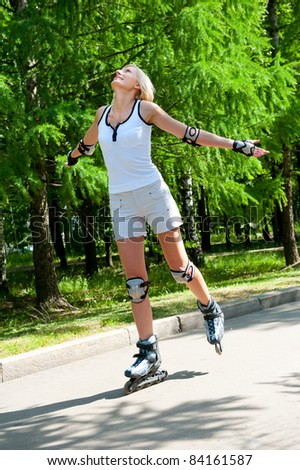 Girl roller-skating in the park at summer - stock photo