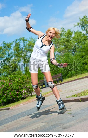 Girl roller-skating in the park, she is still studying, and nearly falls - stock photo