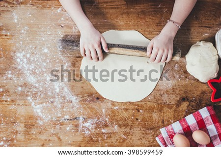 Girl rolling dough with rolling pin - stock photo