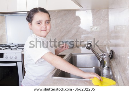 Girl rubs yellow rag sink and countertop water
