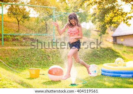 Girl running above a sprinkler, sunny summer back yard - stock photo