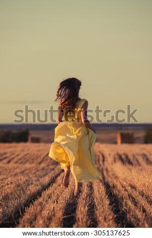 girl running across field in the sunset - stock photo