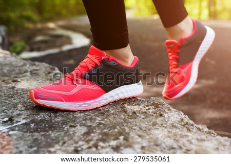 Girl running and jumping in fitness outfit, closeup on legs - stock photo