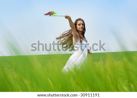 girl running in a green field with colorful hand mill