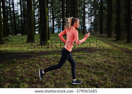 girl running in formation in forest in pink shirt