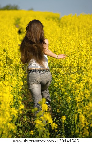 Girl running in the blooming rapeseed field - stock photo