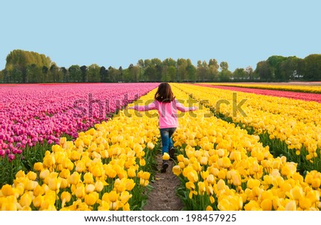 Girl running in yellow tulip field - stock photo