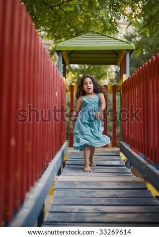 "girl running on a wooden ""bridge"" in a playground - stock photo"