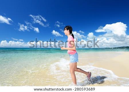 Girl running on beach - stock photo