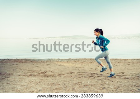 Girl running on sand beach near the sea in summer in the morning. Concept of sport and healthy lifestyle. Space for text in the left part of image