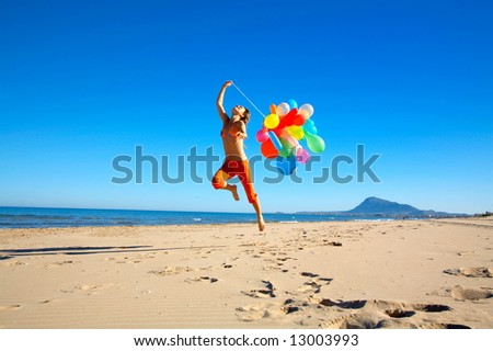 girl running on the beach with colorful balloons