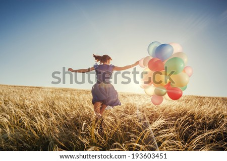 Girl running on the field with balloons at sunset. Happy woman on nature.  - stock photo