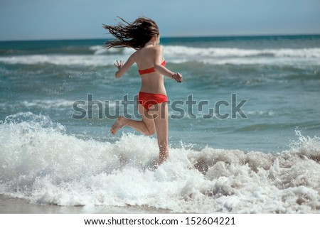 Girl running on the waves on the beach smiling and laughing