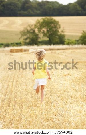Girl Running Through Summer Harvested Field - stock photo