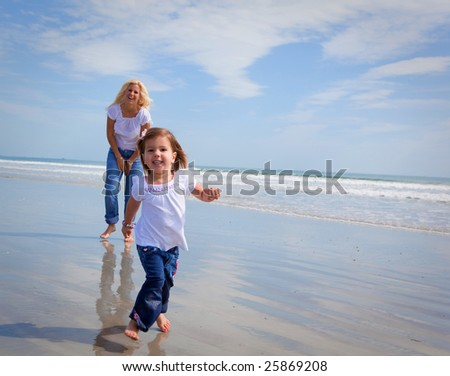Girl running towards the camera. Mom in the background. - stock photo