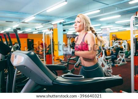Girl runs on treadmill. Active girl in gym runs on treadmill. Athlete cardio activity on treadmill.  - stock photo