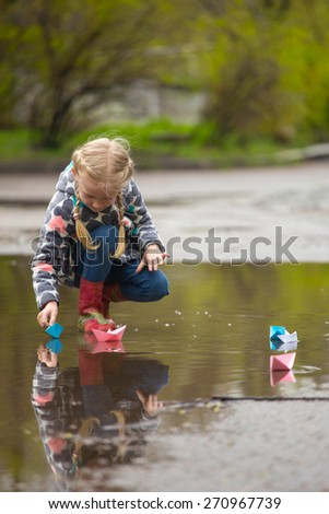 girl runs the pink paper boat in a puddle in the rain, spring  - stock photo