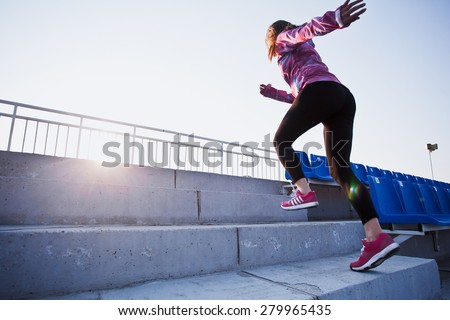 Girl runs upstairs to a sunset. Young woman in sportswear training on a stadium. Copy space. Healthy lifestyle in a city concept - stock photo