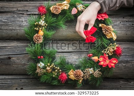 Girl's arm with red bow and decorating rustic log cabin wall and Christmas wreath - stock photo