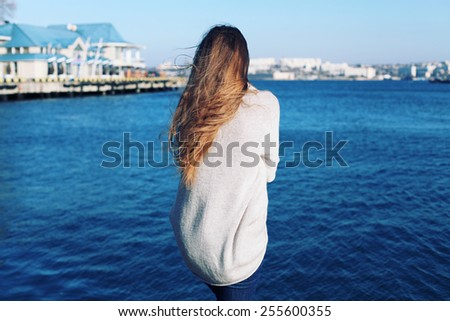 Girl 's back. Posing outdoor in stylish clothes. Hair blowing. Soft light.  - stock photo