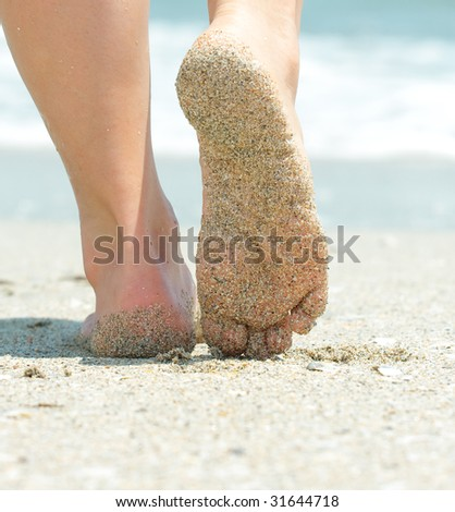 girl's barefoot legs on the sand beach - stock photo
