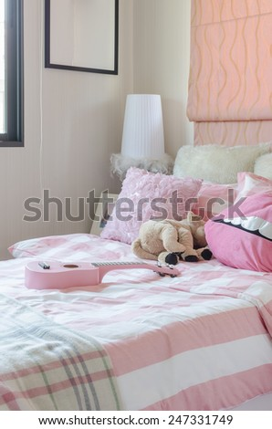 girl's bedroom in pink color with pillows and doll at home - stock photo