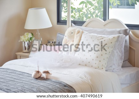 girl's bedroom with ballet shoes and dolls on bed at home