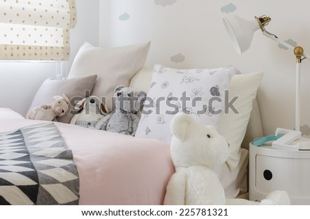 girl's bedroom with dolls on bed at home - stock photo