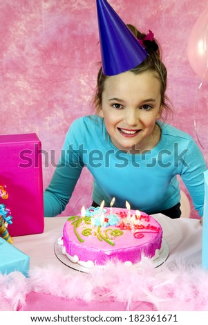 Girl's birthday party celebration with cake and balloons with girl ready to blow out candles