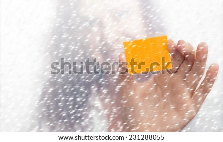 Girl's blurry face and hand with a yellow slip of paper in the snowfall
